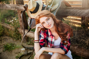 Attractive redhead young woman cowgirl sitting and relaxing outdoors