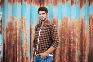 Attractive relaxed young man in checkered shirt standing with hands in pockets