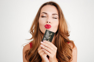 Attractive seductive young woman with red lips sending kiss and holding credit card over white background