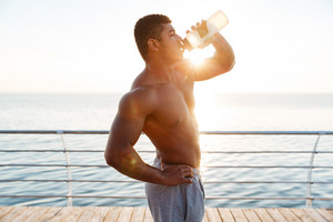 Attractive shirtless muscular african american young man drinking water on pier
