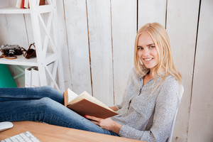Attractive smiling businesswoman reading book while sitting at the workplace in office