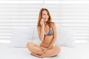 Attractive smiling girl in bikini talking on the phone over white background with pillows