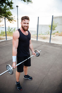 Attractive smiling sportsman standing and holding barbell outdoors