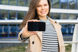 Attractive smiling woman shows the display of the smart phone outdoors. The girl wearing a beige jacket and a striped shirt.