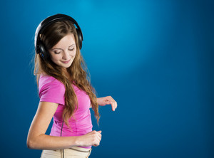 Attractive teenage girl with headphones on blue background. She is listening music.