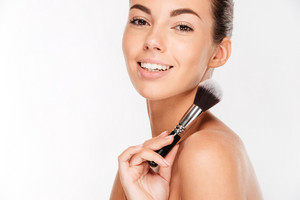 Attractive woman doing make-up on face isolated on white background
