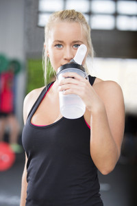 Attractive woman drinking water at fitness gym
