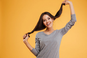 Attractive woman holding to the hair. so happy and funny girl. isolated orange background