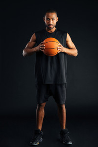 Attractive young african man with basket ball isolated on a black background