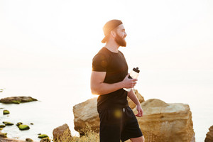 Attractive young bearded sportsman holding bottle of water and standing on the beach