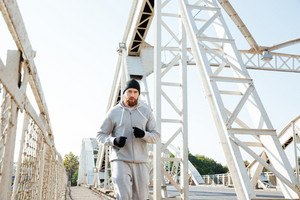 Attractive young bearded sportsman running across the bridge outdoors