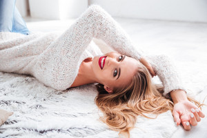 Attractive young blonde woman with red lipstick lying on the floor indoors