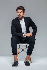 Attractive young bristled man in suit sitting on the chair over grey background