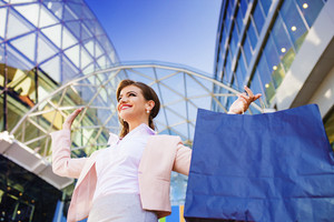 Attractive young business woman with shopping bags in the city