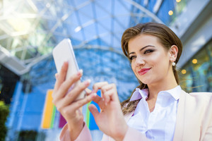 Attractive young business woman with smart phone
