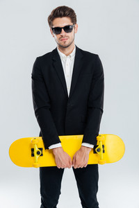 Attractive young businessman in black suit holding yellow skateboard over gray background