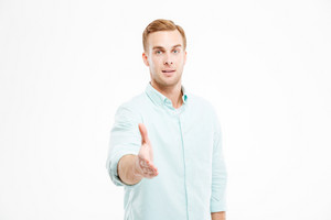 Attractive young businessman standing and giving his hand for handshake