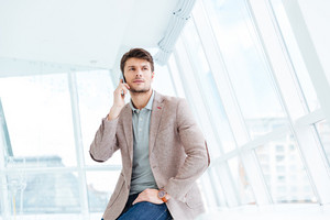 Attractive young businessman talking on mobile phone while sitting indoors