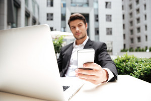 Attractive young businessman using laptop and cell phone in outdoor cafe