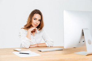 Attractive young businesswoman sitting at the office desk with laptop and looking at camera