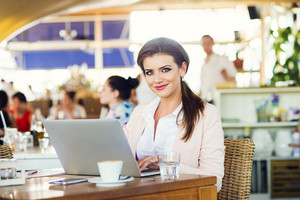 Attractive young businesswoman with notebook in cafe