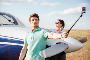 Attractive young couple making selfie using selfie stick while standing near airplane