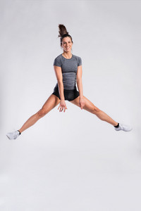 Attractive young fit woman in gray t-shirt and black shorts exercising, jumping high. Slim waist, perfect fit female body. Copy space. Studio shot on gray background.