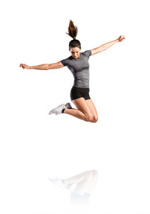 Attractive young fit woman in gray t-shirt and black shorts exercising, jumping high. Slim waist, perfect fit female body. Studio shot on white background, isolated.