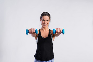 Attractive young fitness woman in black singlet, working out with dumbbells. Slim waist, perfect fit female body. Studio shot on gray background.