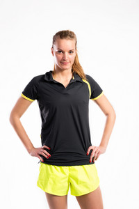 Attractive young fitness woman in black t-shirt and neon yellow shorts, arms on hips. Studio shot on gray background.