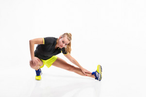 Attractive young fitness woman in black t-shirt and yellow shorts, stretching her legs. Studio shot on gray background.