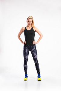 Attractive young fitness woman in black tank top and leggings, arms on hips. Studio shot on gray background.