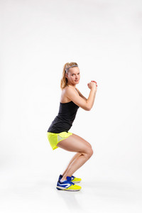 Attractive young fitness woman in black tank top and neon yellow shorts doing squats. Studio shot on gray background.