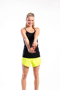 Attractive young fitness woman in black tank top and neon yellow shorts stretching arms. Studio shot on gray background.