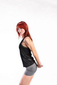 Attractive young fitness woman in black tank top and shorts flexing her arms. Studio shot on gray background.