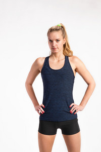 Attractive young fitness woman in blue tank top and black shorts, arms on hips. Studio shot on gray background.