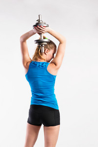 Attractive young fitness woman in blue tank top and black shorts, holding dumbbell. Slim waist, perfect fit female body. Studio shot on gray background. Rear view.