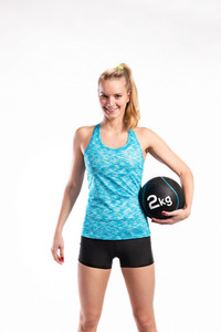 Attractive young fitness woman in blue tank top and black shorts, holding medicine ball. Studio shot on gray background.