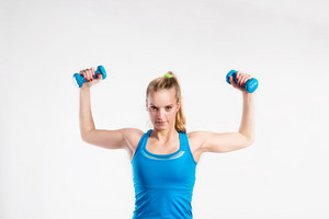 Attractive young fitness woman in blue tank top, holding dumbbells. Slim waist, perfect fit female body. Studio shot on gray background.