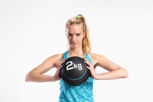 Attractive young fitness woman in blue tank top, holding medicine ball. Studio shot on gray background.