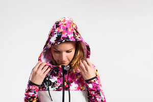 Attractive young fitness woman in colorful hooded sweatshirt. Studio shot on gray background.