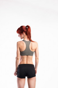Attractive young fitness woman in gray sports bra and shorts. Studio shot on gray background. Rear view.