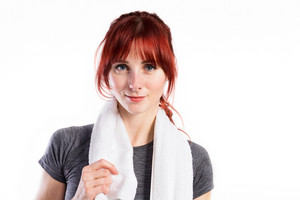 Attractive young fitness woman in gray t-shirt, white towel around her neck. Studio shot on gray background.