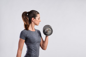 Attractive young fitness woman in gray t-shirt, working out with dumbbell. Slim waist, perfect fit female body. Studio shot on gray background.