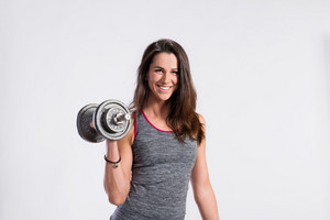 Attractive young fitness woman in gray tank top, holding dumbbell. Slim waist, perfect fit female body. Studio shot on gray background.