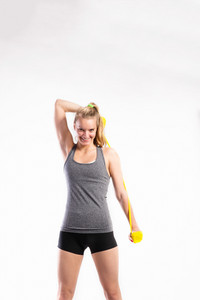 Attractive young fitness woman in gray top and black shorts working out with rubber bands. Studio shot on gray background.