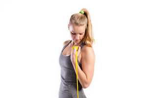 Attractive young fitness woman in gray top working out with rubber bands. Studio shot on gray background.