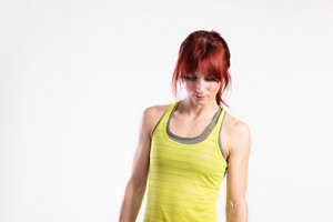 Attractive young fitness woman in green tank top. Studio shot on gray background.
