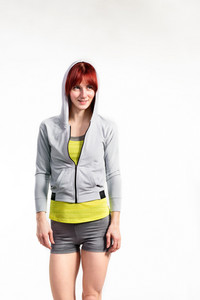 Attractive young fitness woman in hooded gray sweatshirt. Studio shot on gray background.