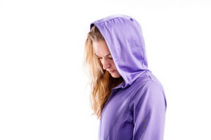 Attractive young fitness woman in purple hooded sweatshirt. Studio shot on gray background.